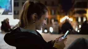坐在市中心在晚上和看照片的可爱的深色的妇女在有触摸屏幕技术的智能手机 免版税库存图片