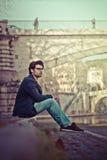坐在市中心的英俊的年轻人 免版税库存照片