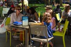 坐在布耐恩特公园比赛表附近的人们 免版税库存照片