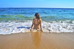 坐在希腊海滩的女孩 库存图片