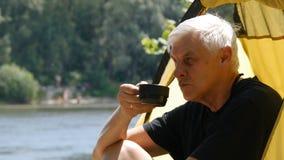 坐在帐篷、饮用的茶或者咖啡的资深男性徒步旅行者 微笑和放松 ?? 远足,旅行,绿色 股票录像