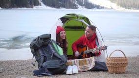 坐在帐篷和唱歌由吉他的年轻可爱的夫妇在山背景  股票视频