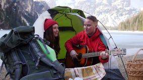 坐在帐篷和唱歌由吉他的年轻夫妇在山背景  股票录像