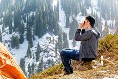 坐在帐篷附近和看通过双筒望远镜的年轻旅游人积雪覆盖的山 免版税库存图片