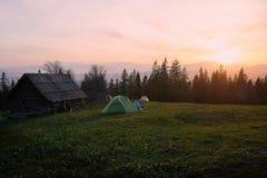 坐在帐篷附近和读书的少妇游人在山的日落 免版税库存图片