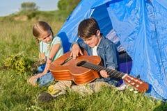 坐在帐篷附近的两个孩子 库存照片