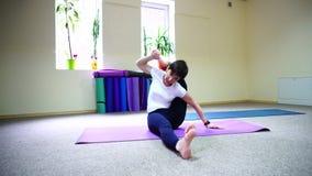坐在席子的地板健身的和执行从瑜伽的年轻美丽的妇女asanas 影视素材