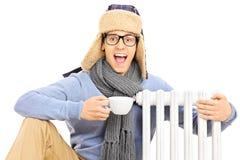 坐在幅射器旁边的年轻人拿着杯子热的茶 免版税库存图片