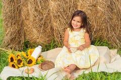 坐在干草堆附近的小女孩有野餐(安纳波利斯Val 免版税库存图片
