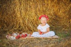 坐在干草堆附近的小女孩 图库摄影