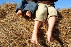 坐在干草捆顶部的小男孩的脚 免版税库存图片