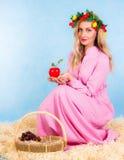 坐在干草的一件桃红色礼服的美丽的少妇 库存照片