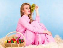 坐在干草的一件桃红色礼服的美丽的少妇 免版税库存照片