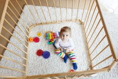 坐在幼儿围栏里面的美丽的矮小的女婴 使用与五颜六色的玩具的逗人喜爱的可爱的孩子 免版税图库摄影