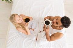 坐在床、愉快的微笑西班牙人和妇女油罐顶部角钢视图上的年轻夫妇饮料咖啡 免版税库存图片