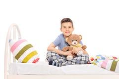 坐在床上和拥抱玩具熊的愉快的小男孩 图库摄影