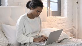 坐在床上和研究膝上型计算机的年轻非洲妇女 股票录像