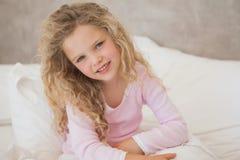 坐在床上的一个微笑的女孩的画象 免版税库存照片