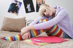 坐在床上的哀伤的十几岁的女孩 免版税库存照片