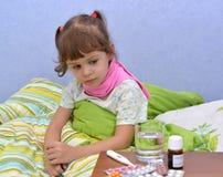 坐在床上的小病的女孩的画象在药物附近 免版税图库摄影