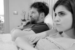 坐在床上的恼怒的夫妇在战斗以后不看彼此 免版税图库摄影