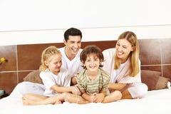 坐在床上的愉快的家庭 图库摄影