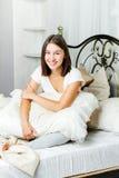 坐在床上的愉快的少妇 免版税库存照片