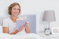 坐在床上的愉快的白肤金发的妇女拿着书 库存照片