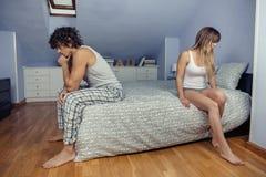 坐在床的反面的恼怒的夫妇 免版税库存照片