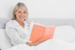 坐在床读书的白肤金发的妇女微笑对照相机 库存照片