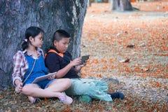 坐在庭院夏时和戏剧片剂的两个亚裔孩子 库存图片