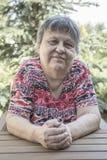 坐在庭院的一个可爱的老妇人 库存图片