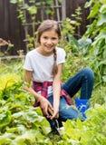 坐在庭院里和用小锄头庭院床的美丽的微笑的十几岁的女孩画象  免版税图库摄影