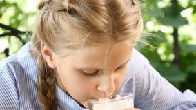 坐在庭院里的一个年轻直率的女孩的画象享用太阳 她拿着一个杯子热巧克力,喝 股票视频