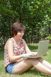 坐在庭院里的亚裔女孩播放笔记本 免版税库存照片