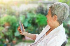 坐在庭院里的亚裔年长妇女拿着智能手机 免版税库存图片