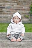 坐在庭院里的俏丽的女婴 库存照片