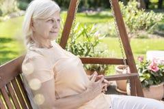 坐在庭院里的病的正面癌症患者 库存照片