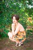 坐在庭院里的礼服的美丽的女孩 免版税库存照片