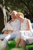 坐在庭院里的资深夫妇 免版税库存图片