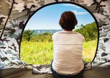 坐在开放旅游帐篷门附近的女孩 图库摄影