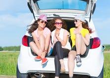 坐在开放树干的年轻可爱的妇女 免版税图库摄影