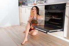 坐在开放烤箱旁边的乏味少妇 免版税库存图片