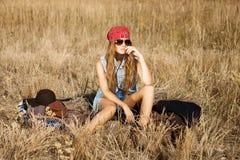 坐在开放领域的美丽的年轻嬉皮的女孩在午间 免版税库存照片