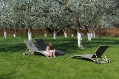 坐在开花苹果庭院里的小女孩 安置放松 库存照片