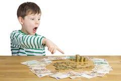 坐在很多货币前面的男孩 库存照片