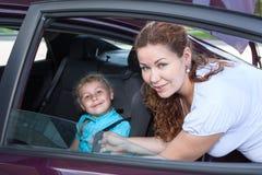 坐在微型汽车位子和母亲帮助的孩子 免版税库存图片