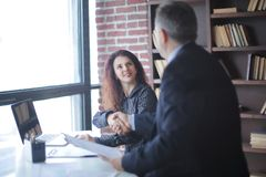 坐在您的书桌的握手经理和客户 库存照片