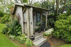坐在惊人的花园里的逗人喜爱的微小的木材古董棚子 免版税库存图片