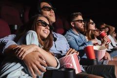 坐在戏院的爱恋的夫妇观看影片和拥抱 库存照片
